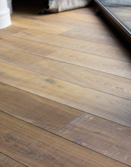 Drewniana dębowa podłoga: Przezroczysta biel Q-3409, szczotkowana w poprzek.